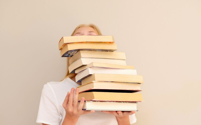 Teenage girl hiding behind big pile of books she wants to read. Booklover or student ready to study concept